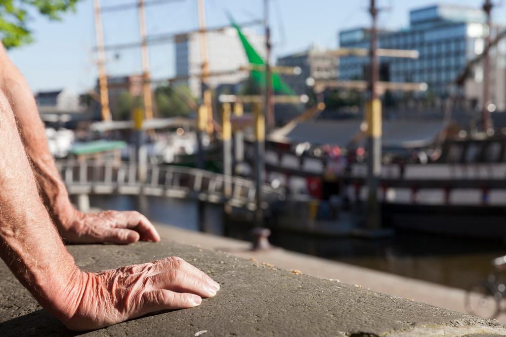 Hände eines Teilnehmers mit Blick auf Hafen
