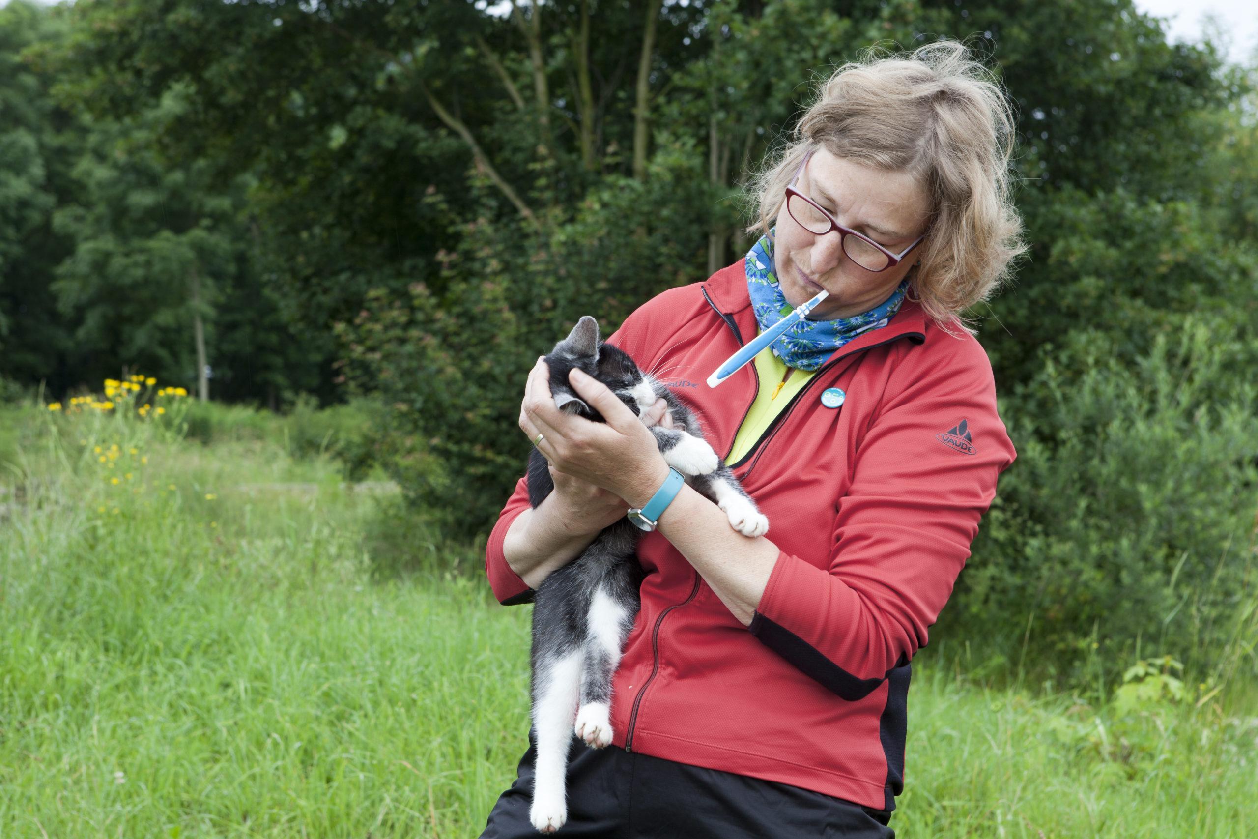 MUT-TOUR Teilnehmerin mit Katze im Arm und Zähne putzend.